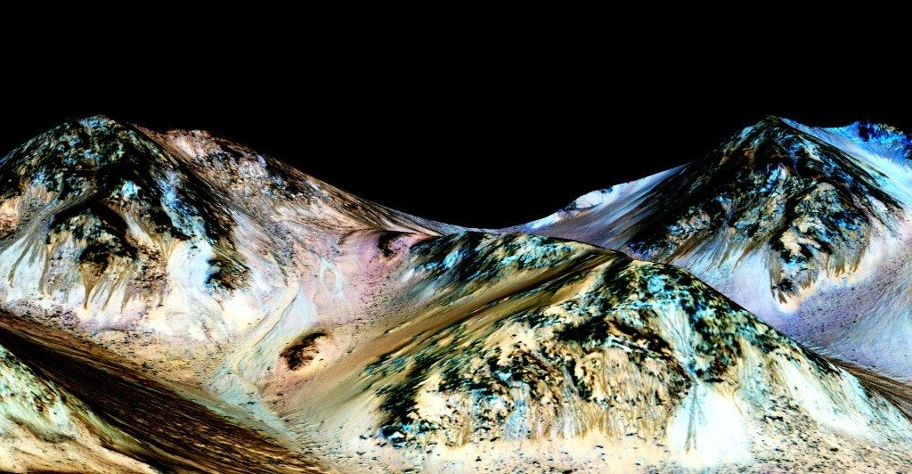 The brown splotchy areas in this shot of Mars' Hale Crater are salt deposits formed by flowing liquid water, NASA scientists recently announced. That Day-Glo blue stuff is pyroxene, a common mineral on Mars. NASA/JPL/UNIVERSITY OF ARIZONA Gallery Image