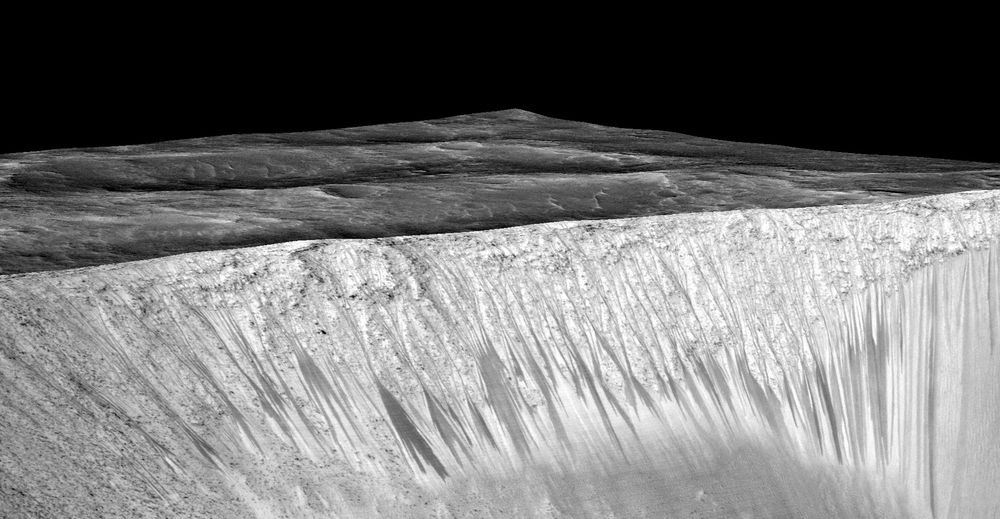 Dark narrow streaks called recurring slope lineae emanating out of the walls of Garni crater on Mars. (NASA/JPL/University of Arizona)