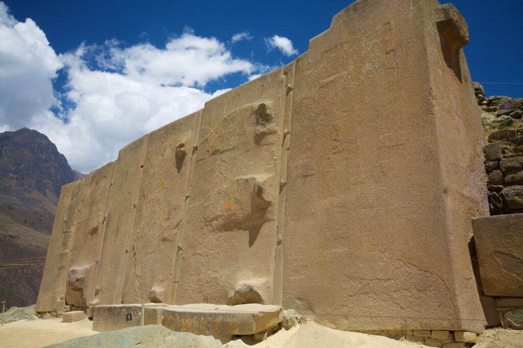 """Ollantaytambo: The temple of the Sun. Just how did ancient mankind achieve this? In this image we have the six red-granite monoliths that were to be part of an unfinished circular wall. The monoliths are separated by """"spacer rocks"""" which prevents them from collapsing during seismic events."""