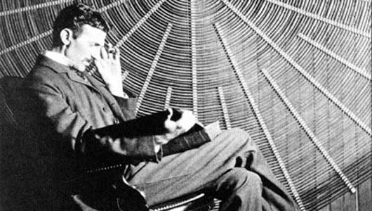 A rare image of Nikola Tesla next to his spiral coil.