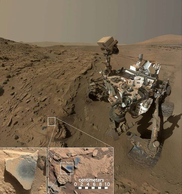 "This scene shows NASA's Curiosity Mars rover at a location called ""Windjana,"" where the rover found rocks containing manganese-oxide minerals, which require abundant water and strongly oxidizing conditions to form. In front of the rover are two holes from the rover's sample-collection drill and several dark-toned features that have been cleared of dust (see inset images). These flat features are erosion-resistant fracture fills containing manganese oxides. The discovery of these materials suggests the Martian atmosphere might once have contained higher abundances of free oxygen than it does now. Credits: NASA/JPL-Caltech/MSSS"