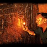 Erich Von Daniken exploring an ancient temple.