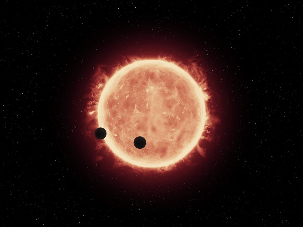 An artist's illustration shows two Earth-sized planets spinning across the face of an M dwarf star called TRAPPIST-1.